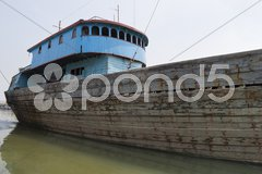 Blue rusty vessel in a canal in Jakarta harbor Stock Photos