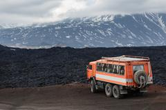 Expedition truck on mountain road on background lava fields and volcanoes Stock Photos