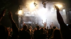Spectator fans cheerfully raise hands up in air at music concert enjoying music Stock Footage
