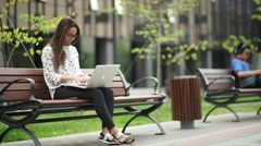 Beautiful girl with a laptop sitting on the street. Remote work Stock Footage