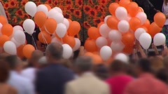 Festival in the city. A lot of people, and orange, and white balloons. Stock Footage
