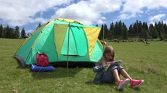 4K Girl Playing Games on Tablet at Camping, Child Using PC Gadget near a Tent Stock Footage