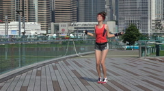 Beautiful sportsgirl with skipping rope in urban modern city slow motion. Stock Footage