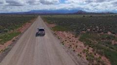 Following SUV Through Desert Towards Distant Mountains Stock Footage
