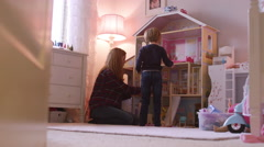 A little girl and her mom playing with a giant dollhouse in her room Stock Footage