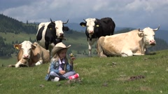 4K Farmer Child Pasturing Cows In Mountains, Cowherd Girl Relaxing by Cattle  Stock Footage
