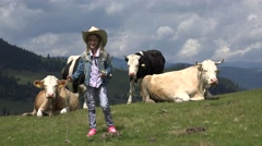 4K Farmer Girl Pasturing Cows on Meadow, Cowherd Child with Cattle in Mountains Stock Footage