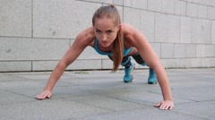 Young pretty woman doing fitness push-ups sport exercises on grey background Stock Footage