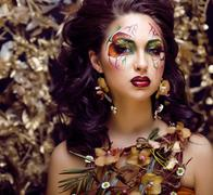 Beauty woman with face art and jewelry from flowers orchids close up, creative Stock Photos
