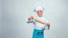 Chef cook child 7-8 years dancing with rolling-pin on white background Stock Footage