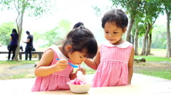 Child two cute little girls eating ice cream together in the park Stock Footage