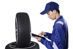 Mechanic with tablet examining tires Stock Photos