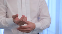 Man wears cufflinks on the cuffs of his shirt. Close up Stock Footage