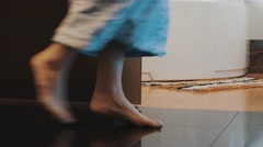 View of woman in bathrobe walk into bathroom on tiptoe and sit down on bath Stock Footage
