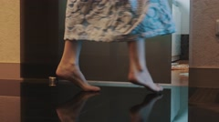 Girl in bathrobe walk in bathroom on tiptoe and sit down on bath. Turn on light Stock Footage