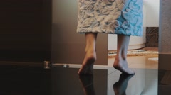 Girl in bathrobe walk in bathroom on tiptoe, sit down on bath. Turn on light Stock Footage