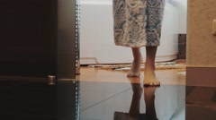 Girl in blue bathrobe stand up from white bath walk out of bathroom on tiptoe Stock Footage