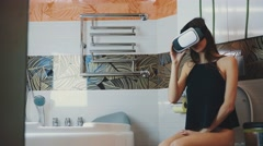 Girl sit on toilet. Looking in virtual reality glasses. Bathroom. Virtual world Stock Footage