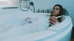 Girl take bath full of foam in bathroom. Smoke electronic cigarette. Bathtub Stock Footage
