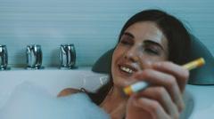 Girl take bath full of foam in bathroom. Smoking electronic cigarette. Enjoy Stock Footage