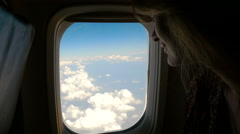 Young woman looking up at the clouds from the airplane window. 4K Stock Footage