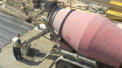 Workers loading wheelbarrow with concrete from the mixer truck by Sheyno. Stock Footage