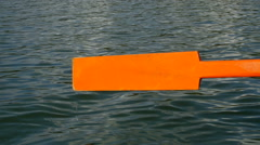 Old wooden paddle bounces into lake water Stock Footage