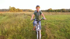 Child in cycle helmet riding bike looking cheerfully in camera in sunset meadow Stock Footage