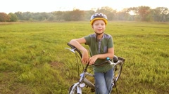 Child in cycle helmet talking cheerfully to camera near his bike Stock Footage