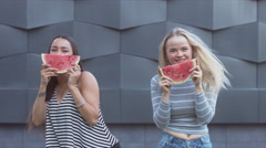 4K MED portrait of two young girls enjoying a watermelon in the street Stock Footage