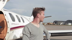 Man Stands Next to a Private Plane on a Background of a Passing Passenger Plane Stock Footage