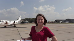 Girl Guide is on the Airfield on the Background of a Passing Helicopter Stock Footage