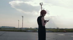 A Girl Stands at the Airfield and Typing on Phone Stock Footage