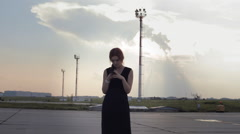 Girl Stands on the Background of the Sunset Sky and Dials on the Phone Stock Footage