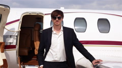 Businessman in Black Suit Stands Beside His Private Jet Arkistovideo