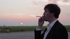 Businessman in Black Suit Smokes an Electronic Cigarette at the Sunset and Stock Footage