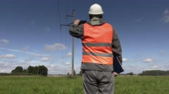 Electrician take pictures under high-voltage lines Stock Footage