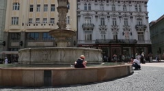 Little girl washing herself off sitting on edge of fountian in square Stock Footage