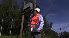 Electrician talking on the phone near high-voltage lines and transformer Stock Footage