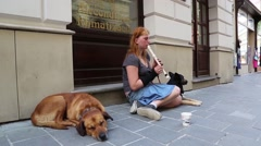 Homeless redheaded girl playing flute with dog nearby Stock Footage