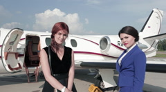 Two Girls Stand Near the Plane and Laugh Stock Footage