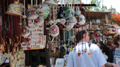Handmade souvenires hanging up at local market Stock Footage