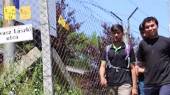 Group of 3 syrian refugees walking happily next to fence Arkistovideo