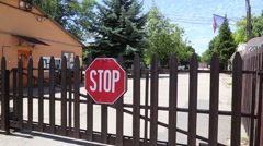 Establishing Shot of front gate with stop sign Stock Footage