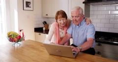 4k, Senior couple using a laptop at home and browsing holiday websites. Stock Footage