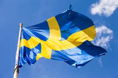Swedish flag waving in the wind on a blue sky background Stock Photos