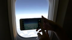 The girl photographs the the clouds from an airplane windows. HD Stock Footage