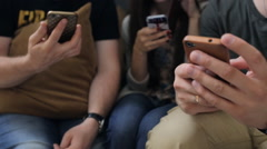 Three persons sit on sofa and keep cell phones in their hands Stock Footage
