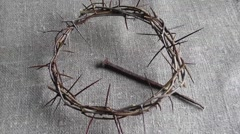 Zoom out over crown of thorns and large nail on burlap. Stock Footage