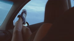 4K UHD Relaxed teen on road trip travel puts legs out car window Stock Footage